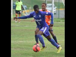 Kingston College's Ronaldo Robinson (front) gets by Dunoon Technical's Quala Rose during their ISSA/Digicel Manning Cup match at the Breezy Castle Field in downtown Kingston. Kingston College were leading 2-0 when the referee called a halt to the match in the 55th minute because of lightning in the area, on Tuesday, September 17.