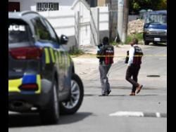 Police process the scene on Nelson Road, St Andrew, where a man from Greenwich Farm was killed by gunmen yesterday.