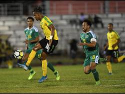 Jamaica's Peter-Lee Vassell (left) attempts to control the ball while being pursued by Guyana's Samuel Cox in their League B Group C Concacaf Nations League encounter at the Montego Bay Sports Complex on Monday night.