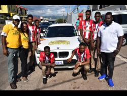 Carlington Sinclair (left) and wife Marsha (second left) show their allegiance to their alma mater BB Coke High with the decorations on their car. Looking on are Patrick Sappleton (right), CEO of SAP Sports, with members of the Ben Francis Cup winning team.