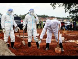 Public health officers wearing protective clothing at the grave site of a man who died from the coronavirus in Nairobi, Kenya. Attendance at funerals in Jamaica and much of the world are now being attended by a small number of persons, a measure instituted to slow the spread of the virus.