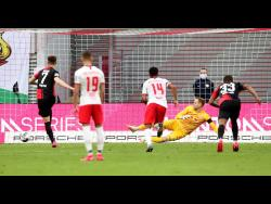 Berlin's Krzysztof Piatek (left) scores his side's second goal from the penalty spot during the German Bundesliga match between RB Leipzig and Hertha BSC at the Red Bull Arena in Leipzig, Germany, yesterday. The game ended in a 2-2 draw.