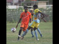 Tivoli Garden's Jermaine Johnson makes a pass while  Waterhouse player Colorado Murray  moves in, during their  Red Stripe Premier League encounter at the Edward Seaga Complex.