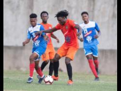 Rodico Wellington (second right) of Tivoli Gardens gets by Lamar Walker (left) of Portmore United during their Red Stripe Premier League match played at the Spanish Town Prison Oval on Sunday, March 1.