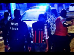 Police personnel investigate the triple murder in Tryall Heights, near Lauriston, St Catherine, on Sunday evening. Two girls and their grandmother were slain.