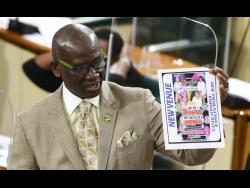 Minister of Local Government Desmond McKenzie holds up a flyer advertising a party in contravention of Jamaica's coronavirus laws.