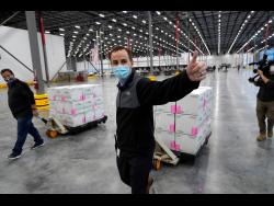 A worker gives a thumbs up while transporting boxes containing the Moderna COVID-19 vaccine to the loading dock for shipping at the McKesson distribution centre in Olive Branch, Mississippi, yesterday. It is expected to be given out starting today. The Pfizer and BioNTech vaccine was rolled out last week. (AP Photo/Paul Sancya, Pool)