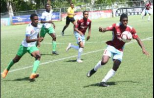 Chantomoi Taylor (right) of St George's College controls the ball as Rashawb Streete from Norman Manley High looks on during their ISSA/Digicel Manning Cup match at Winchester Park  on October 7. St George's won the match 4-0.