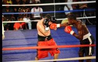 Jamaica's Jermaine Bowen (right) lands a straight right to the head of his Miami, Florida-based opponent Angel Martinez during an I-Fight Promotions fight night at the Karl Hendrickson Auditorium at Jamaica College in St Andrew last Saturday.