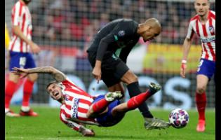 Atletico Madrid's Angel Correa falls as Liverpool's Fabinho goes for the ball during a first leg, round of 16, of the Champions League match between Atletico Madrid and Liverpool at the Wanda Metropolitano stadium in Madrid, yesterday.