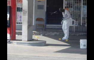 A police investigator at the scene of yesterday's shooting along Red Hills Road in Kingston.