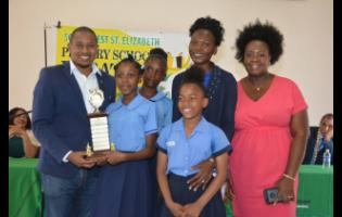 Floyd Green (left) presents the first place trophy to Natallia Samuels (second left) of Mountainside Primary School, following the finals of the inaugural South West Primary School Debate Competition at the Black River Parish Library in St Elizabeth last Thursday. Sharing the moment are students Tiwana Robinson (back) and Kayla Dennis, as well as teachers Phylicia Ebanks (second right) and Sameika Forbes.