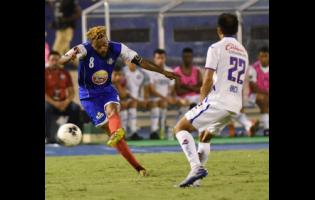 Portmore United captain Ricardo Morris (left)  tries to get past Rafael Baca (right) of Cruz Azul in  the ScotiaBank Concacaf Champions Cup match at the National Stadium yesterday.