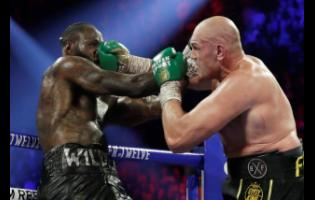 In this February 22, 2020 file photo, Tyson Fury, of England, lands a right to Deontay Wilder (left) during a WBC heavyweight championship boxing match in Las Vegas. Boxing promoter Bob Arum says he plans to stage a card of five fights on June 9 at the MGM Grand.