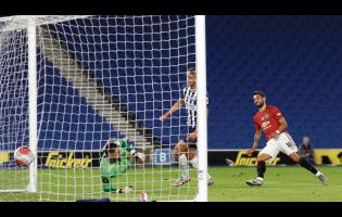 Manchester United's Bruno Fernandes (right) scores his side's third goal during the English Premier League match between Brighton & Hove Albion and Manchester United at the AMEX Stadium in Brighton, England, on Tuesday, June 30, 2020.