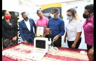 Chief Medical Officer at the Sir John Golding Rehabilitation Centre, Dr Rory Dixon (third right), explains the use of the portable ultrasound machine to  (from left) Latoya Aquart-Foster, CHASE project manager; Johann Heaven, CEO, Proven Wealth; Kecia Taylor, past services director, Rotary Club of St Andrew North; Lori Chuck, past president, Rotary Club of St Andrew North; and Denise Harris, chief marketing officer, C&WJ Credit Union, at the presentation of the equipment to the centre on July 3.
