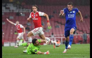Leicester's Jamie Vardy attempts to take the ball past Arsenal's goalkeeper Emiliano Martinez during the English Premier League match between Arsenal and Leicester at Emirates Stadium in London, England, Tuesday, July 7, 2020.