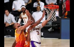 Los Angeles Lakers forward Anthony Davis (3) is fouled by Utah Jazz centre Rudy Gobert (left) during the first half of an NBA basketball game on Monday, August 3, in Lake Buena Vista, Florida.