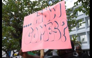 This placard was held aloft by a demonstrator during a protest on Trafalgar Road in Kingston in July 11 as persons sought answers about their high light bills. Complaints against the Jamaica Public Service Company have increased by196 per cent.