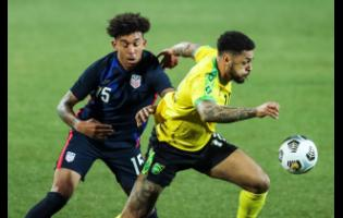 USA's Chris Richards (left) duels for the ball with Jamaica's Andre Gray during the international friendly soccer match between USA and Jamaica at SC Wiener Neustadt stadium in Wiener Neustadt, Austria, Thursday, March 25, 2021.