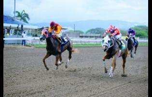 Further and Beyond (left), ridden by Dane Nelson, wins the Prince Consort Stakes  ahead of Billy Whizz, ridden by Anthony Thomas, over seven furlongs at Caymanas Park yesterday.