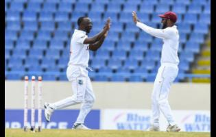 West Indies bowler Kemar Roach (left) celebrates with captain Kraigg Brathwaite after one of the three wickets he claimed to help reduce Sri Lanka to 169 all out on day-one of the first Test in North Sound, Antigua on Sunday, March 21.
