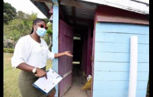 Mellesha Pinto, teacher at the Hall's Delight Primary School, shows the pit latrine that children had to use at the school before the handover of modern facilities