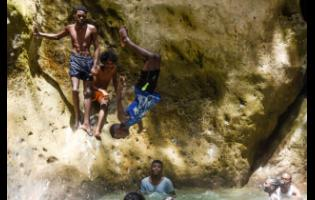 Rohan Wilson is full flight at Cane River Falls in St Andrew yesterday.