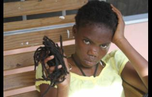 Princess Nzinga Candace King, 19, with a handful of her dreadlocks she save after she was allegedly trimmed by a cop.