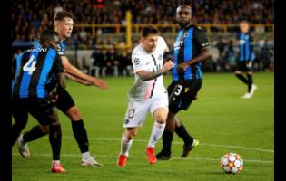 PSG's Lionel Messi (centre) goes after the ball against Brugge's Stanley Nsoki (left) and Eder Balanta (right) during the Champions League Group A soccer match at the Jan Breydel stadium in Bruges, Belgium, yesterday. The game ended 1-1.