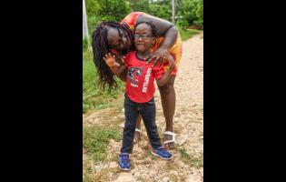 Shanice Rowe poses with her son, Lashaun Rowe, in Zambia, Central Village, St Catherine. Lashaun suffers from a rare medical condition, Walker-Warburg Syndrome, a rare multisystem disorder that tends to claim the lives of children by age three. Lashaun celebrates his sixth birthday this Saturday.