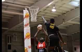 Jamaica Men's player Kyle Foster defends against Afeisha Noel of Trinidad and Tobago  during the Sunshine Series Invitational exhibition netball match  at the National Indoor Sports Centre in St Andrew last night.
