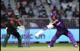 Scotland's batsman Chris Greaves (right) plays a shot as Bangladesh's wicketkeeper Nurul Hasan looks on during the  Twenty20 World Cup first round match between Bangladesh and Scotland in Muscat, Oman on Sunday, October 17.