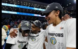 Chicago Sky head coach James Wade (centre) celebrates with Candice Parker (right) and Kahleah Copper after defeating the Phoenix Mercury in Game 4 of the WNBA Finals to become champions on  Sunday, October 17 in Chicago.