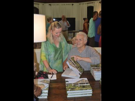 Photographer Cookie Kinkead (right) jokes with Katrin Casserly, chairman of Hanover Charities, at her book signing.