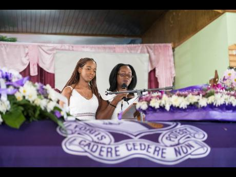 Cousin Kadine Octable (left) stands by for support as Kadian Brown-Williams,Twayne's aunt, delivers the rememberance.