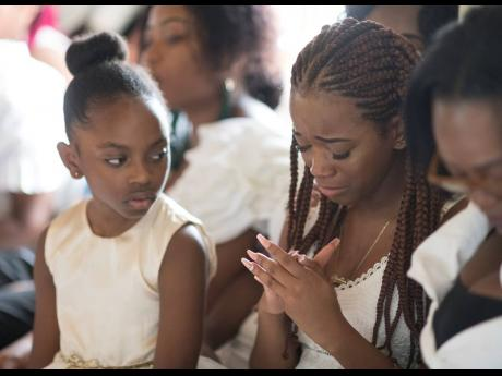 Adrianna Ali looks on as Kadine Octable (right) is overcome with grief as she mourns her cousin Twayne Crooks.