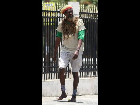 Without shoes and with a 30-pound chain around his neck, Derrick 'Black X' Robinson, in this 2018 photo,  walked from St Mary to Kingston in his quest to make Tacky a National Hero.