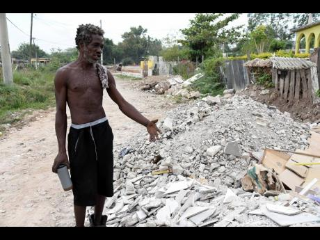 Anthony Panter, a resident of New Haven in St. Andrew, points to debris that he used to patch roads.