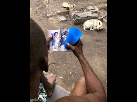 Stephen Reid gazes at old pictures of his son.