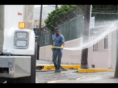 Kemar Cain washes the sidewalks, walls and bus stops along Oxford Road in St Andrew on Sunday. The Government is spearheading a massive clean-up effort to help contain the spread of COVID-19.