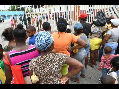 A crowd at the gate of New Hope Preparatory School on North Street in Kingston on Tuesday to collect food being distributed under the PATH programme.
