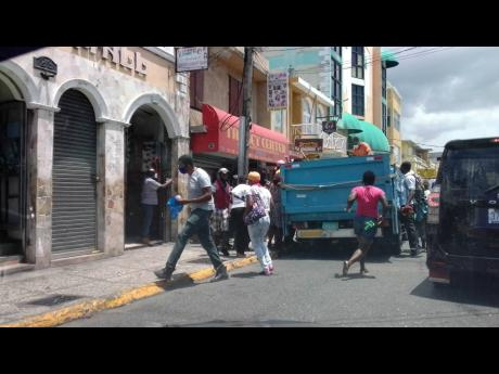 Persons rush toward the 'giveaway truck' in downtown MoBay on Wednesday.