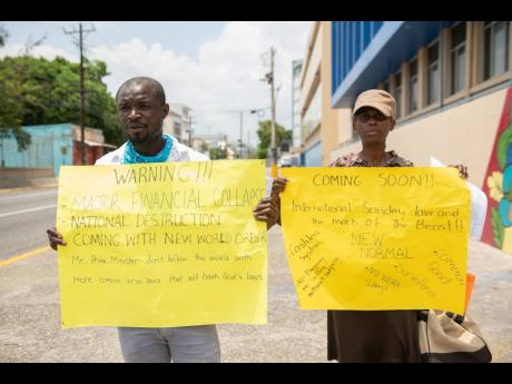 Jermaine Allen (left) and Jacqueline Murray protest what they believe to be an impending new world order in front of The Gleaner Company Media Limited.