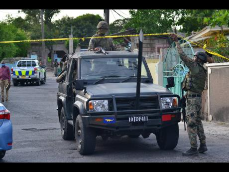 Soldiers patrol a section of August Town, St Andrew, where a disabled woman died, allegedly at the hands of the security forces yesterday.