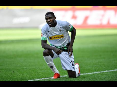 Moenchengladbach's Marcus Thuram gets up after taking the knee after scoring his side's second goal during the German Bundesliga match between Borussia Moenchengladbach and Union Berlin in Moenchengladbach, Germany, Sunday, May 31, 2020.