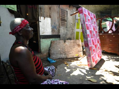 Nichola Pink's mother, Patricia Shaw, is at a loss for words as she sits in the yard where the couple lived in Chestnut Lane, Denham Town.