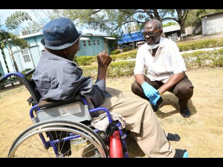 Desmond McKenzie, the minister of local government, talks to a resident of the Golden Age Home in Vineyard Town, Kingston, on March 30, a few weeks after Jamaica recorded its first COVID-19 case.