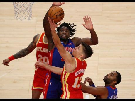 Bogdan Bogdanovic of the Atlanta Hawks tries to lay up a shot against Detrot Pistons' Isaiah Stewart in the second half of a NBA match at the State Farm Arena in Atlanta, Georgia, on December 28, 2020.